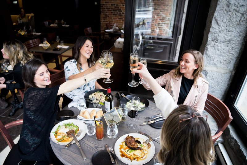 Four women celebrate and eat in Verses Bistro