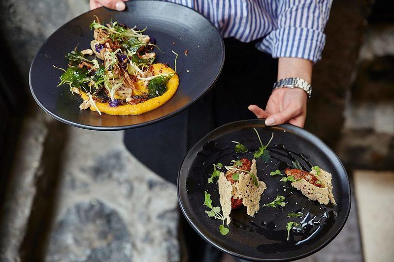 Un serveur tient les plats dans les versets Bistro